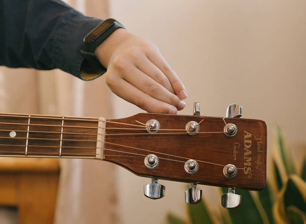guitariste accordant son instrument à cordes