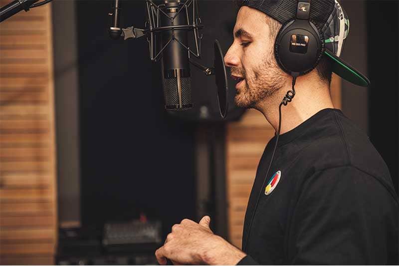 un chanteur avec un casque entrain d'enregistrer une chanson