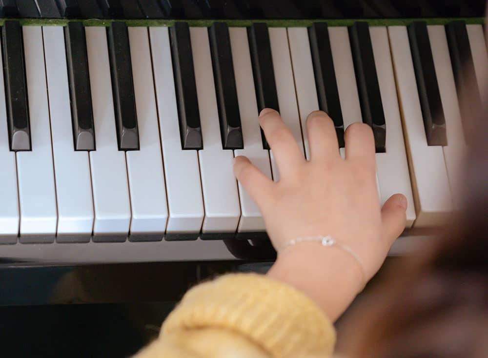 une main posée sur un clavier de piano